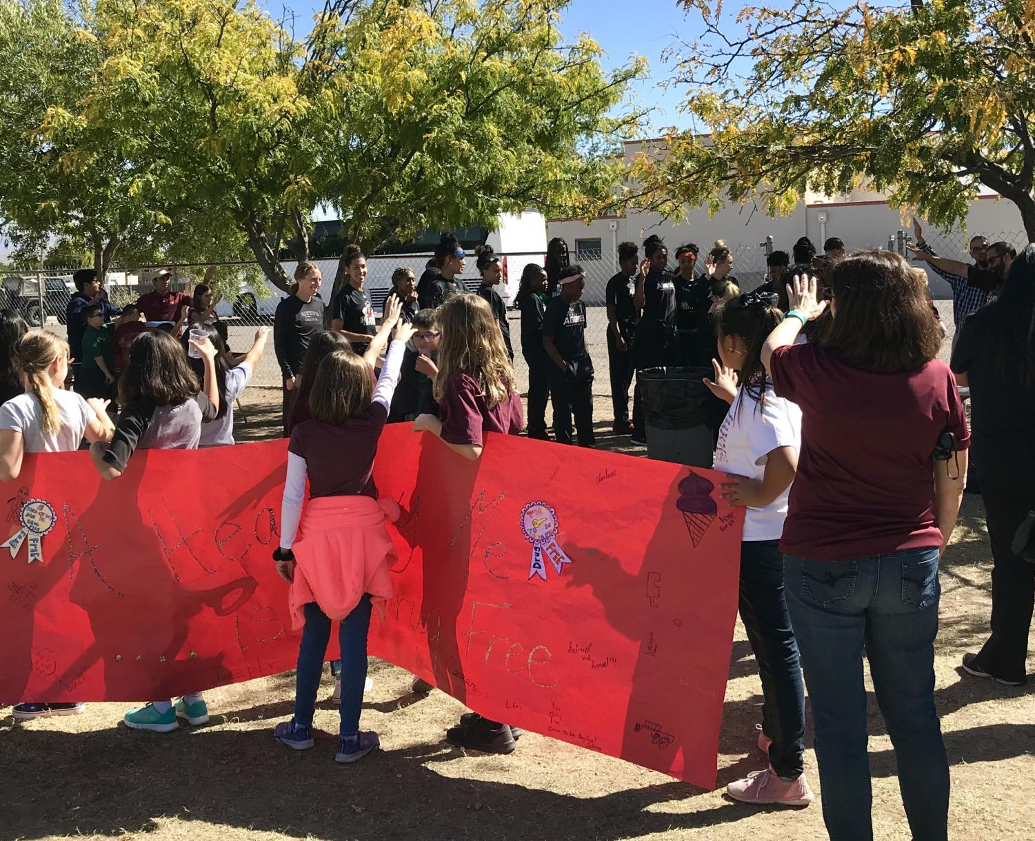 Las Cruces Catholic School students and staff extend their arms to bless the New Mexico State Women's Basketball Team.