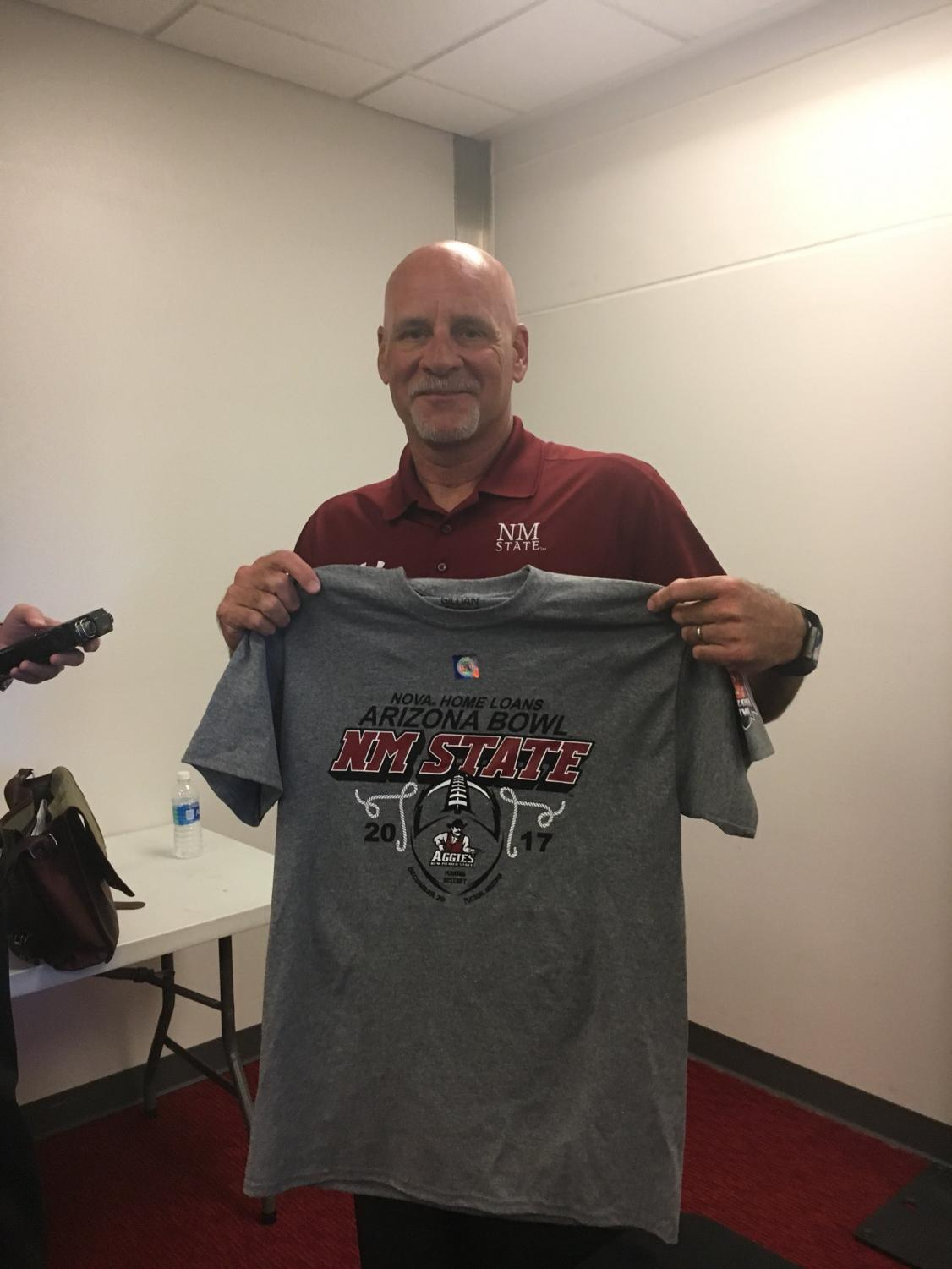 NMSU head coach Doug Martin takes picture with NOVA Home Loans Arizona Bowl t-shirt. The Aggies will be making their first bowl appearance since 1960.