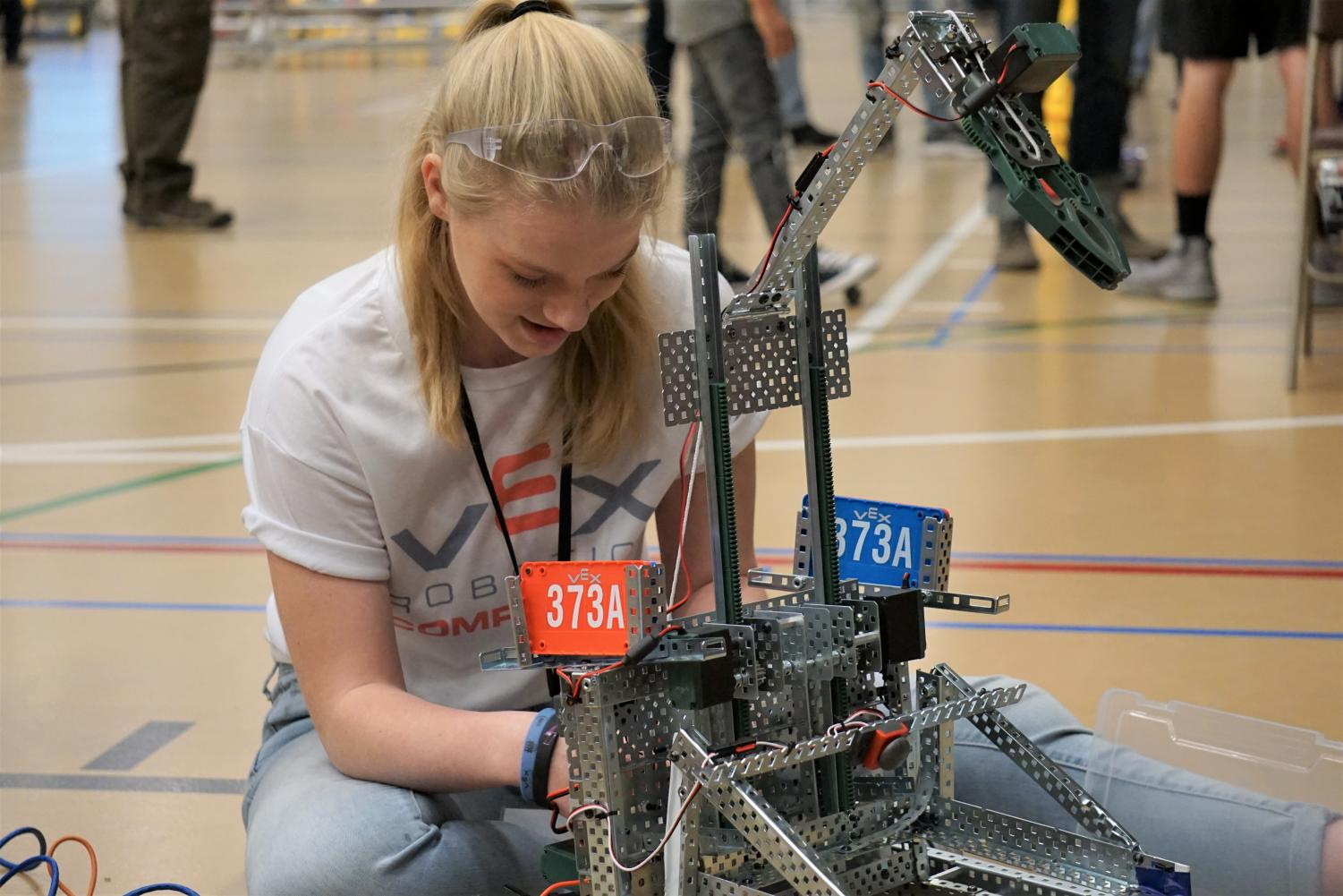 A student adds the final touches on her robotic design at the VEX Robotics Competition State Championship