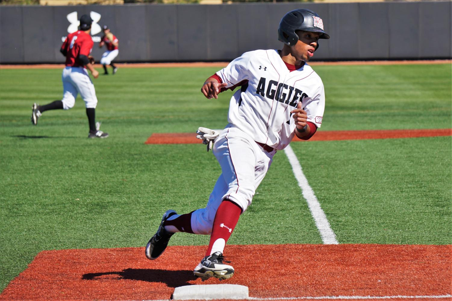 NMSU senior Marcus Still rounds third in hopes to score on Sunday afternoon at Presley Askew Field; the Aggies won the game 23-4.