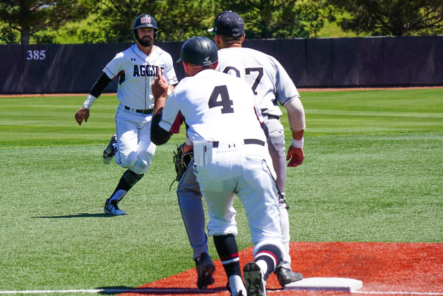 A NMSU base-runner gets ready to slide in to third base during Sunday's series finale against Utah Valley.