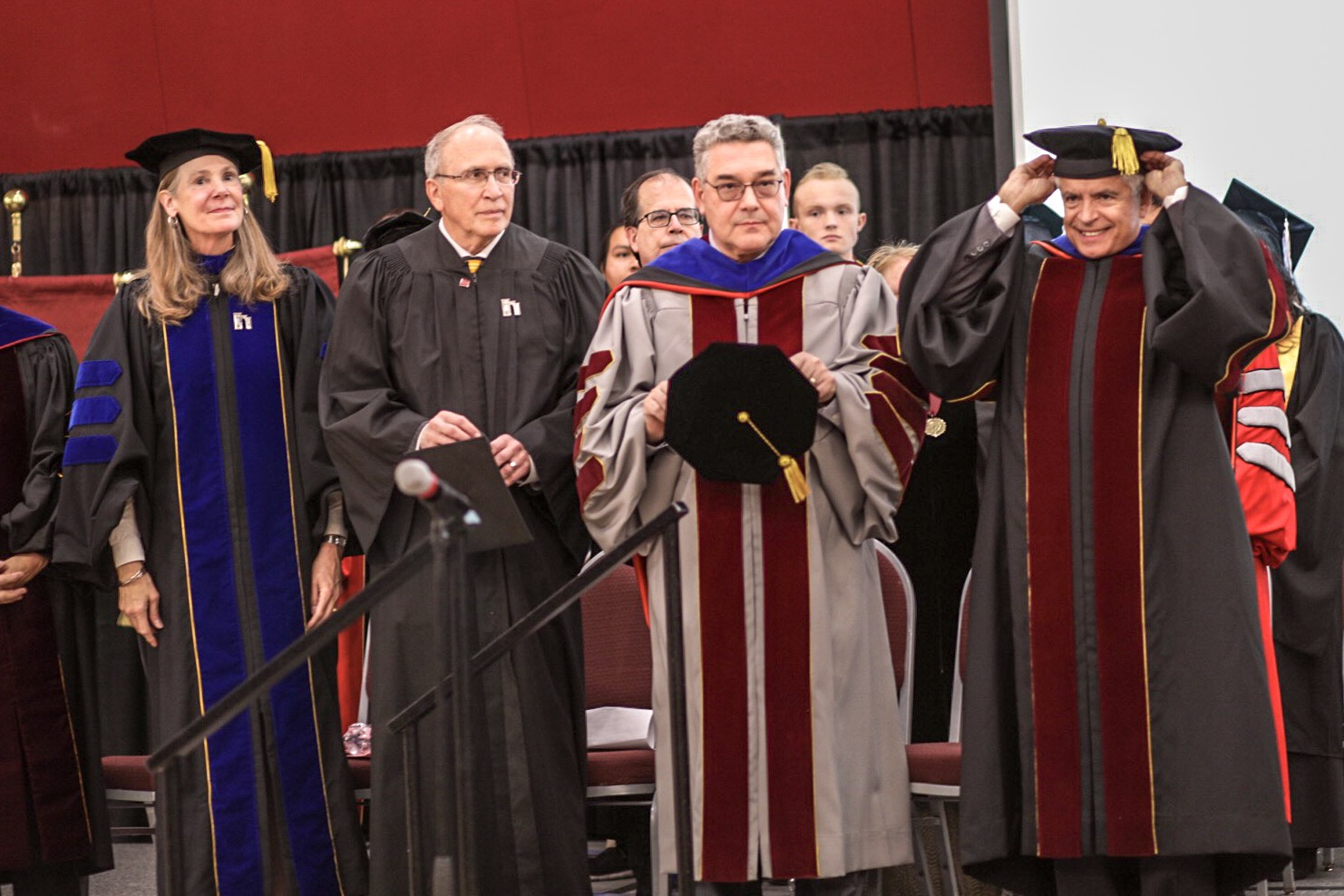 President John D. Floros and Chancellor Dan Arvizu stand with colleagues wearing Academic Regalia at NMSU inauguration.