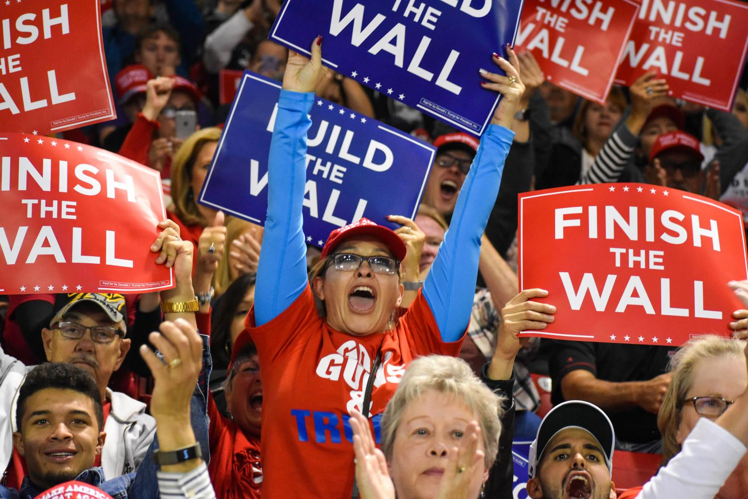 Attendees of the Trump rally in El Paso, TX. hold signage in favor of a border wall.
