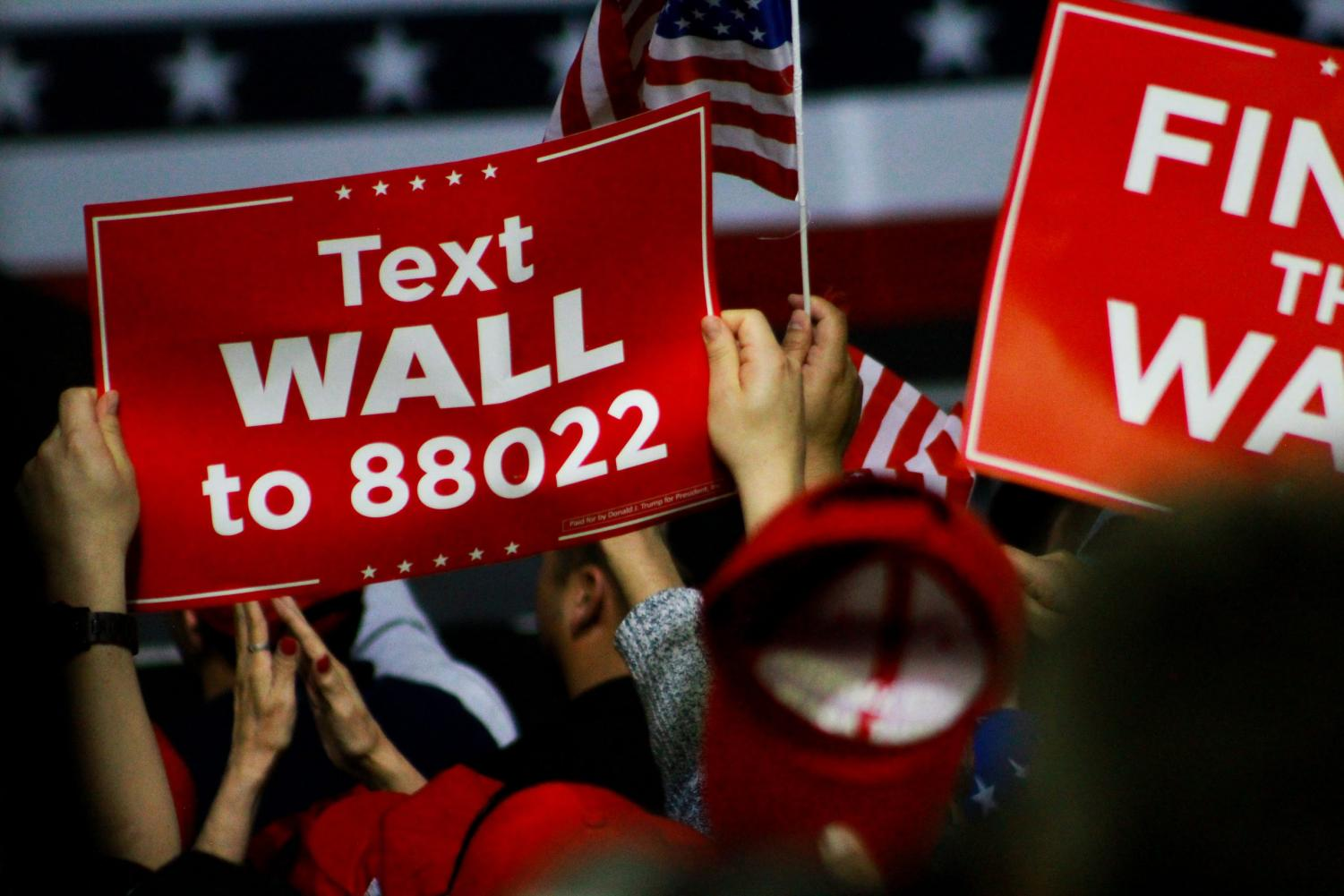 Trump supporters wave signage in favor of a border wall and Make America Great Again hats at the President's rally Monday.