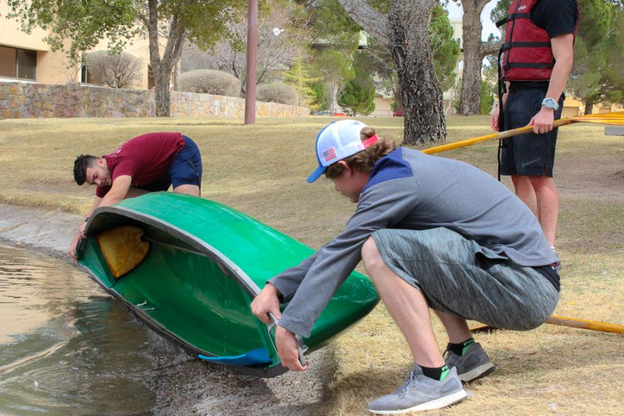 Casey and a team member dumping the water out of the canoe.