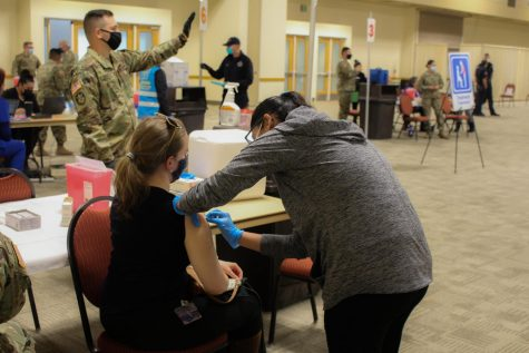 A woman receives a COVID-19 Vaccine while armed guards aid with distribution on Jan. 27, 2021.