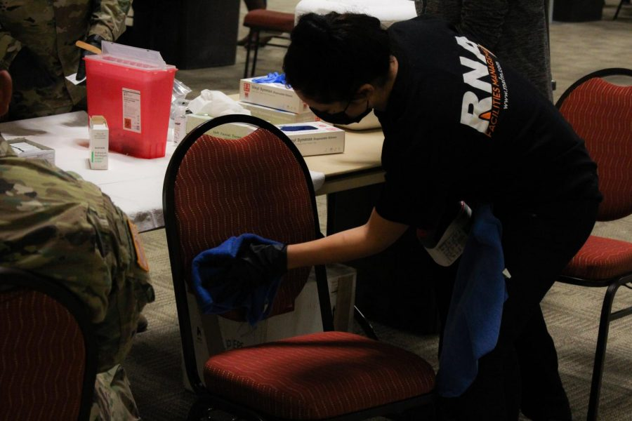 Volunteers clean vaccinations chairs after each patient.