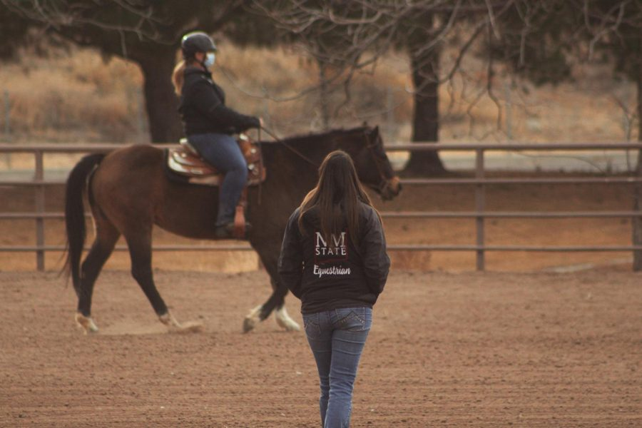 NMSU Equestrian team coach Hannah Swarthout looks at her riders as they practice going around The Arena.