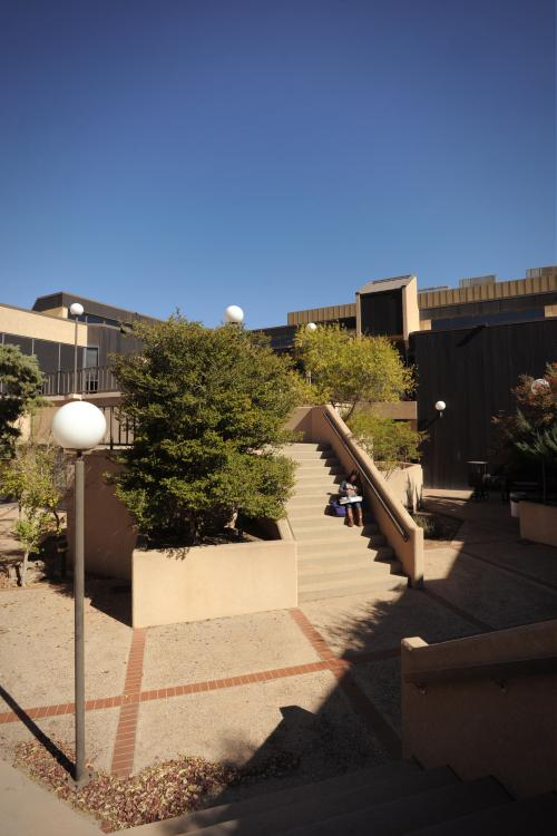 A student reads a book outside on the steps of the NMSU Carlsbad branch. (Image Courtesy of NMSU News Center.)