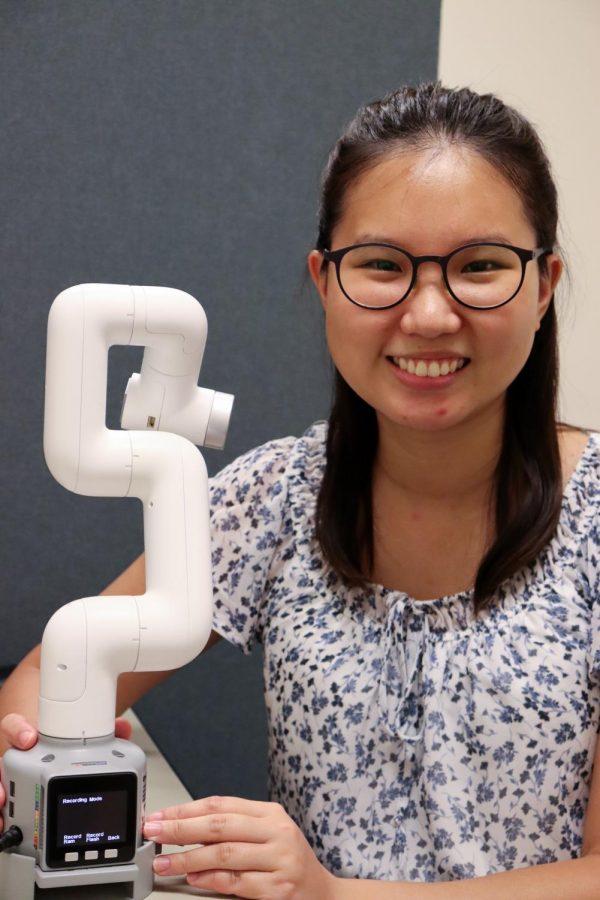 Rachel Au, psychology graduate student, and the robotic arm.