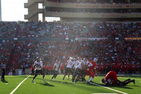 Quarterback Jonah Johnson drops back to pass against a ferocious Lobos defense.